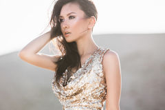 Beautiful asian woman in fashion luxury shiny dress in desert Stock Photo