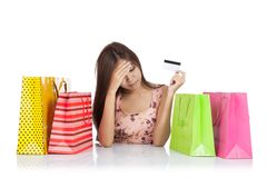 Beautiful Asian woman fed up with a credit card and shopping bag. S on table isolated on white background stock images