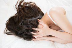 Beautiful asian woman feel unwell painful and ill. Lying on bed at home, bedroom background Stock Photo