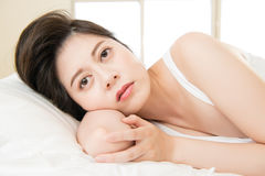 Beautiful asian woman feel unwell sickness and ill. Lying on bed at home, bedroom background Royalty Free Stock Image