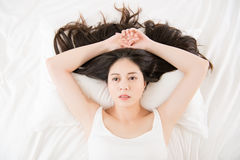 Beautiful asian woman feel unwell sickness and ill. Lying on bed at home, bedroom background Stock Image