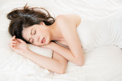 Beautiful asian woman feel unwell sickness and ill. Lying on bed at home, bedroom background Royalty Free Stock Images