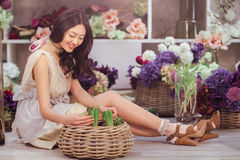 Beautiful asian woman florist in lacy white dress in flower store Royalty Free Stock Images