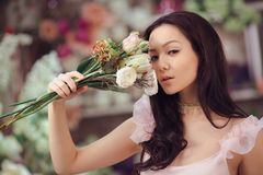 Beautiful asian woman florist in pink dress with bouquet of flowers in hands in flower store Stock Image