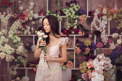 Beautiful asian woman florist in pink dress with bouquet of flowers in hands in flower store Stock Photography