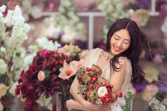 Beautiful asian woman florist in white dress with bouquet of flowers in hands in flower store Royalty Free Stock Photo