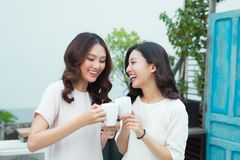 Beautiful asian woman friends holding plastic cup of ice black c. Beautiful asian women friends holding plastic cup of ice black coffee on balcony royalty free stock image