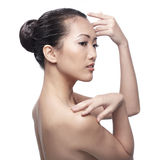 Beautiful Asian woman gently touching her face. Royalty Free Stock Photo