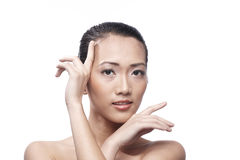 Beautiful Asian woman gently touching her face. Stock Images