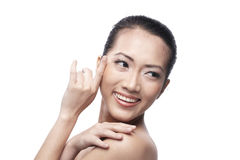 Beautiful Asian woman gently touching her face. Royalty Free Stock Image