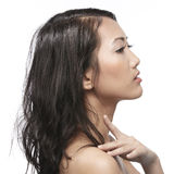Beautiful Asian woman gently touching her face. Royalty Free Stock Images