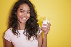 Beautiful asian woman with a glass of fresh milk. Close up portrait of beautiful asian woman with a glass of fresh milk on yellow background Stock Photo