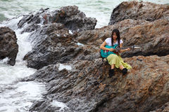 Beautiful asian woman with a guitar on beach Royalty Free Stock Image
