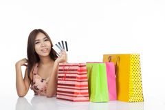 Beautiful Asian woman happy with credit cards and  shopping bags. Beautiful Asian woman happy with credit cards and shopping bags on table  isolated on white Stock Images
