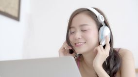 Beautiful asian woman happy earphone listening music with relax and enjoy in the bedroom. Girl fun headphone playing radio on laptop computer, lifestyle stock video