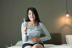 Beautiful asian woman happy and smiling after testing pregnancy test in her bedroom royalty free stock photo