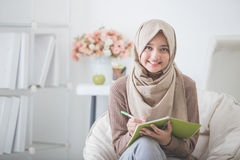 Beautiful asian woman with head scarf writing something Stock Photo