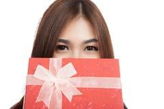 Beautiful Asian woman hiding behind red gift box Royalty Free Stock Photos