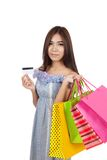 Beautiful Asian woman hold shopping bags show a credit card Royalty Free Stock Photos