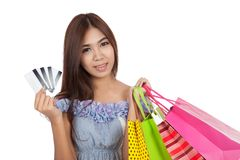Beautiful Asian woman hold shopping bags show credit cards Royalty Free Stock Images