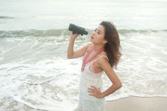 Beautiful asian woman holding  binoculars on the beach . Royalty Free Stock Photo