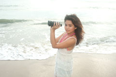 Beautiful asian woman holding  binoculars on the beach . Royalty Free Stock Image
