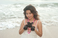 Beautiful asian woman holding  binoculars on the beach . Royalty Free Stock Photography