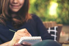 A beautiful Asian woman holding black pencil and writing on notebook sitting in modern cafe with blur green vertical garden Royalty Free Stock Photos