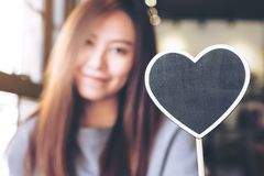 A beautiful asian woman holding a blank heart shape blackboard sign with feeling happy Royalty Free Stock Image