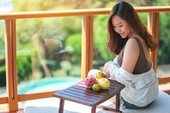 A beautiful asian woman holding fruits while enjoy sitting at balcony. With the sea view background royalty free stock photography