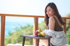 A beautiful asian woman holding fruits while enjoy sitting at balcony. With the sea view background stock photo