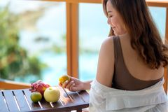 A woman holding fruits while enjoy sitting at balcony with the sea view background. A beautiful asian woman holding fruits while enjoy sitting at balcony with royalty free stock photos
