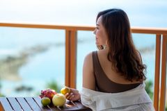A woman holding fruits while enjoy sitting at balcony with the sea view background. A beautiful asian woman holding fruits while enjoy sitting at balcony with royalty free stock photography