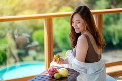 A woman holding fruits while enjoy sitting at balcony with the sea view background. A beautiful asian woman holding fruits while enjoy sitting at balcony with stock photography