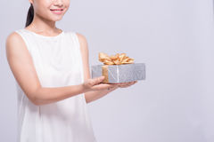Beautiful Asian woman holding gold gift box on white background Stock Photography