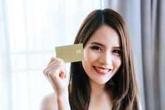 Beautiful Asian woman holding golden credit card. Beautiful Asian woman holding golden blank credit card Royalty Free Stock Photo