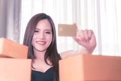 Beautiful woman holding golden blank credit card for online shopping. Beautiful Asian woman holding golden blank credit card for online shopping Royalty Free Stock Image