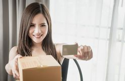 Beautiful Asian woman holding golden credit card for online shopping. Beautiful Asian woman holding golden blank credit card for online shopping Royalty Free Stock Images