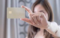 Beautiful Asian woman holding golden credit card. Beautiful Asian woman holding golden blank credit card Stock Photography