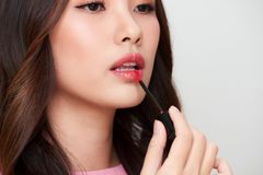 Beautiful asian woman holding red lipgloss and applying it.  Stock Image