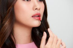 Beautiful asian woman holding red lipgloss and applying it.  Stock Photography