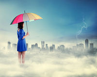 Beautiful asian woman holding umbrella standing over the cloud. Looking at the city Royalty Free Stock Image