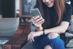 A beautiful Asian woman holding and using at smart phone sitting cross leg in modern cafe. Closeup image of a beautiful Asian woman holding and using at smart royalty free stock image