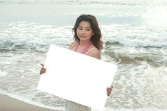 Beautiful asian woman holding a white billboard on the beach . Stock Photography
