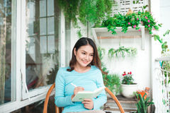Beautiful asian woman at home writing and working with diary Stock Photo