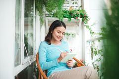 Beautiful asian woman at home writing and working with diary Stock Photos