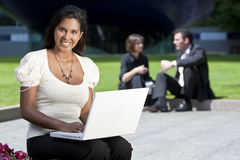 Beautiful Asian Woman on Laptop. A beautiful young Asian woman using her laptop outside while behind her out of focus are an executive couple sitting having Stock Photos