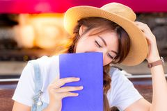 Beautiful asian woman is laughing the story in pocket book that stock photo