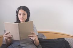 Beautiful Asian woman listening music with headphone and reading book relaxing on the bed. royalty free stock photo