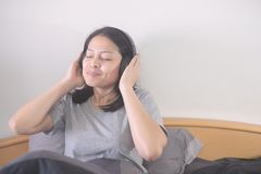 Beautiful Asian woman listening music with headphone relaxing on the bed.. stock image